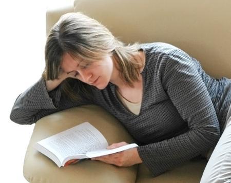 flickan läser en bok i soffan